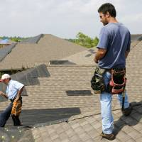 Photo - STORM DAMAGE: Jim Beres, left, and Allen Vollmer, right, of Good Guys Construction working with Aegis Roofing, look at temporary roof repairs done at 2608 Southern Hills Drive in Moore, Oklahoma, Tuesday, May 11, 2010. Vollmer and Beres were doing frame repairs, including replacing the home's chimney block, after the home was damaged in severe weather the previous day. Photo by Nate Billings, The Oklahoman ORG XMIT: KOD