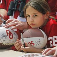 Photo - Jocie Rea McCuen, 9, from Wichita, Kansas, hopes for autographs before the University of Oklahoma Sooner's (OU) Spring Football game at Gaylord Family-Oklahoma Memorial Stadium on Saturday, April 16, 2011, in Norman, Okla.  