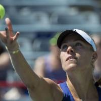 Photo - Angelique Kerber, from Germany, tosses the ball to serve to Caroline Garcia, of France, during second round play at the Rogers Cup tennis tournament Wednesday, Aug. 6, 2014 in Montreal. (AP Photo/The Canadian Press, Paul Chiasson)