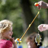 Photo - CHILDREN: Sabra Frederick, 5, of Choctaw gets help taking a fish off her line during a fishing derby for kids in Choctaw, Okla., Saturday, June 20, 2009. Photo by Bryan Terry, The Oklahoman ORG XMIT: KOD