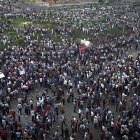 Photo -   Protesters gather in Tahrir square in Cairo, Egypt, Friday, Oct. 12, 2012. Thousands of supporters and opponents of Egypt's new Islamist president clashed in Cairo's Tahrir Square on Friday, hurling stones and concrete and swinging sticks at each other in the first such violence since Mohammed Morsi took office more than three months ago.(AP Photo/Khalil Hamra)