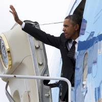Photo - President Barack Obama waves as he boards Air Force One at Andrews Air Force Base, Md., Wednesday, Feb. 26, 2014, en route to St. Paul, Minn. In Minnesota he is expected to speak at Union Depot rail and bus station with a proposal asking Congress for $300 billion to update the nation's roads and railways, and about a competition to encourage investments to create jobs and restore infrastructure as part of the President's Year of Action. (AP Photo/Jacquelyn Martin)