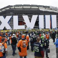 Photo - Fans arrive for the NFL Super Bowl XLVIII football game between the Seattle Seahawks and the Denver Broncos at MetLife Stadium Sunday, Feb. 2, 2014, in East Rutherford, N.J. (AP Photo/Seth Wenig)