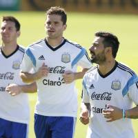 Photo - Argentina's Ezequiel Lavezzi, right, jogs with teammates Lionel Messi, left, and Fernando Gago, center, during a training session in Vespesiano, near Belo Horizonte, Brazil, Saturday, June 28, 2014.  Argentina plays in group F of the 2014 soccer World Cup. (AP Photo/Victor R. Caivano)
