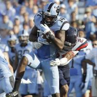 Photo - North Carolina's Quinshad Davis (14) catches a pass as Liberty's Wesley Scott (21) defends during the first half of an NCAA college football game in Chapel Hill, N.C., Saturday, Aug. 30, 2014. (AP Photo/Gerry Broome)