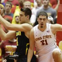 Photo - Michigan forward Mitch McGary, left, grabs a rebound in front of Iowa State forward Georges Niang during the first half of an NCAA college basketball game on Sunday, Nov. 17, 2013, in Ames, Iowa. (AP Photo/Charlie Neibergall)