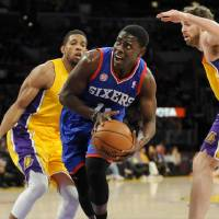 Photo - Philadelphia 76ers guard Jrue Holiday, center, gets by Los Angeles Lakers guard Darius Morris, left, and forward Pau Gasol, right, of Spain, as he battles to the basket in the first half of an NBA basketball game, Tuesday, Jan. 1, 2013, in Los Angeles. (AP Photo/Gus Ruelas)