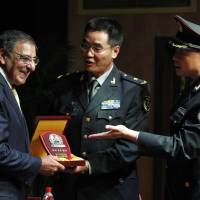 Photo -   U.S. Defense Secretary Leon Panetta, left, receives a plaque after he addresses cadets at the PLA Engineering Academy of Armored Forces in Beijing, Wednesday, Sept. 19, 2012. U.S. Defense Secretary Panetta is telling Chinese troops that America's new military focus on the Asia Pacific, including plans to put a second radar system in Japan, is not an attempt to contain or threaten China. (AP Photo/Larry Downing, Pool)