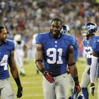 Photo - New York Giants defensive end Justin Tuck (91) talks with teammates Terrell Thomas (24) and Aaron Ross (31) as he leaves the field after the first half of a preseason NFL football game against the New York Jets, Saturday, Aug. 24, 2013, in East Rutherford, N.J. (AP Photo/Bill Kostroun)