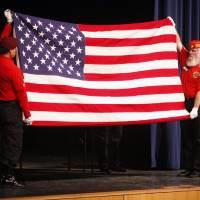 Photo - Gary Hanson, left, and Terry Farmer demonstrate how to fold a flag during a patriotic flag folding demonstration and flag presentation at Southmoore High School.