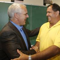 Photo - Aaron Cosar, right, greets former Oklahoma Gov. Brad Henry, left, at The Education and Employment Ministry (TEEM), where Cosar works as a life-skills instructor, in Oklahoma City, Monday, June 24, 2013. Henry, who commuted Cosar's life sentence and signed his parole after Cosar served nearly 25 years in prison for the shooting death of an Ada, Okla. man after a night of drinking when Cosar was 19 years old, surprised the ex-convict by dropping by the classroom where Cosar now teaches life skills to other former inmates. (AP Photo/Sue Ogrocki)