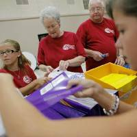 Photo - Church members Kayla Tinsley, Linda Henson, George Henson (from left) and Anna Pennington (far right) stuff bags with school supplies at Capitol Hill Baptist Church in south Oklahoma City.  JOHN CLANTON - John Clanton