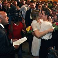 Photo - Just after midnight, Denver Mayor Michael Hancock, left, performs a civil union vows ceremony for Sonja Semion, center left, and her partner Courtney Law at the Webb Municipal Building in Denver, Wednesday May 1, 2013. In March 2013, the Colorado General Assembly passed SB-11, the Colorado Civil Union Act, which provides committed same-sex couples with legal protections and responsibilities. The act went into effect on May 1, 2013. (AP Photo/Brennan Linsley)