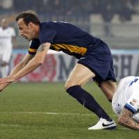 Photo - Inter Milan's Mauro Icardi, right, is fouled by Hellas Verona Greek defender Evangelos Moras during a Serie A soccer match at the Bentegodi stadium in Verona, Italy, Saturday, March 15, 2014. (AP Photo/Felice Calabro')
