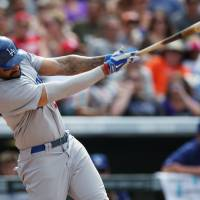 Photo - Los Angeles Dodgers' Matt Kemp follows through with his swing after connecting for an RBI-single against the Colorado Rockies in the fifth inning of a baseball game in Denver on Sunday, July 6, 2014. (AP Photo/David Zalubowski)