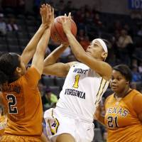 Photo - West Virginia guard Christal Caldwell (1) shoots between Texas guard Celina Rodrigo (2) and forward Nekia Jones (21) in the first half of an NCAA college basketball game in the semifinals of the Big 12 Conference women's college tournament in Oklahoma City, Sunday, March 9, 2014.(AP Photo/Sue Ogrocki)