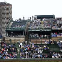 Photo - FILE - This May 17, 2013 file photo shows spectators watching a Chicago Cubs baseball game from several of the rooftop bleachers across the field from Wrigley Field in Chicago. The owners of the Chicago Cubs say they're moving forward with plans to renovate and expand Wrigley Field, despite the threat of lawsuits by the owners of the adjacent rooftop venues overlooking the 100-year-old ballpark. Chairman Tom Ricketts, whose family owns the north-side Chicago team, said Thursday, May 22, 2014, that the Cubs will submit a revised expansion plan to the Commission on Chicago Landmarks that includes the team's original proposal to add several outfield signs and additional bleacher seats.  (AP Photo/Charles Rex Arbogast, File)