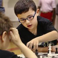 Photo - Alexander Bonner moves his chess piece as Gage Crowson considers his next move. Bonner is a first-grader at Cleveland Bailey Elementary School. Crowson is a first-grader at Townsend Elementary School.