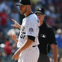 Photo - After being ejected from the game for hitting Atlanta Braves' Evan Gattis with a pitch, Colorado Rockies relief pitcher Nick Masset, front, hands the ball to third base umpire Paul Emmel in the ninth inning of the Rockies' 10-3 victory in a baseball game in Denver on Thursday, June 12, 2014. (AP Photo/David Zalubowski)