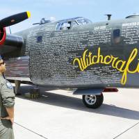 Photo - U.S. Air Force Captain Asif Kausar looks at a B-24J Liberator on display Friday at Wiley Post Airport in Bethany. Photos By Steve Gooch, The Oklahoman