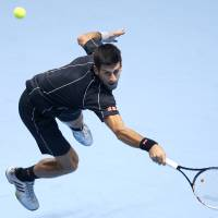 Photo - Novak Djokovic of Serbia plays a return to Juan Martin Del Potro of Argentina during their ATP World Tour Finals tennis match at the O2 Arena in London, Thursday, Nov. 7, 2013. (AP Photo/Kirsty Wigglesworth)