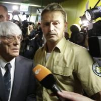 Photo - Formula One boss Bernie Ecclestone leaves the regional court in Munich, southern Germany, Tuesday, Aug.5, 2014. German prosecutors said Tuesday that they will accept dropping the bribery case against Ecclestone in exchange for a US dollar 100 million payment by the Formula One boss, and judges were considering whether to close his trial. Ecclestone went on trial at the Munich state court in late April on charges of bribery and incitement to breach of trust — which could, if he were convicted, carry a sentence of up to 10 years in prison. (AP Photo/Matthias Schrader)