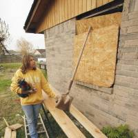Photo - Linda McCanless props boards and leans a shovel against plywood to hold it over a missing window in the house where she and Kenneth Walker Jr. live Wednesday, Nov. 16, 2011, in Newcastle.  The room and most of his house is just as it was after being hit by a tornado May 24  STEVE SISNEY - THE OKLAHOMAN