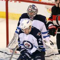 Photo - Winnipeg Jets defenseman Grant Clitsome blocks the puck in front of the Winnipeg net during second period NHL hockey action Saturday Feb. 9, 2013.  (AP Photo/The Canadian Press, Fred Chartrand)