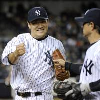 Photo - New York Yankees pitcher Masahiro Tanaka, left, reacts with second baseman Brian Roberts after Roberts made a play to get out Baltimore Orioles' Ryan Flaherty to end the sixth inning of a baseball game Wednesday, April 9, 2014, at Yankee Stadium in New York. (AP Photo/Bill Kostroun)