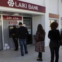Photo - People queue to use an ATM machine outside of a Laiki Bank branch in Larnaca, Cyprus, Saturday, March 16, 2013. Many rushed to cooperative banks which are open Saturdays in Cyprus after learning that the terms of a bailout deal that the cash-strapped country hammered out with international lenders includes a one-time levy on bank deposits. The move, decided in an extraordinary meeting of the finance ministers of the 17-nation eurozone in the early hours Saturday, is a major departure from established policies. Analysts have warned that making depositors take a hit threatens to undermine investors' confidence in other weaker eurozone economies and might possibly lead to bank runs. (AP Photo/Petros Karadjias)