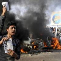Photo - Opponents of Egyptian President Mohammed Morsi hold pamphlets urging a