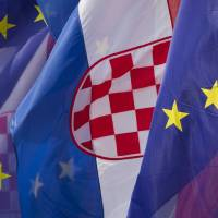 Photo - Croatian and the EU flags are seen at an intersection in Zagreb, Croatia, Saturday, June 29, 2013. Croatia is to join the European Union on July 1, 2013. (AP Photo/Darko Bandic)
