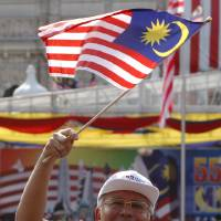 Photo - FILE - In this Friday, Aug. 31, 2012 file photo, Malaysian Prime Minster Najib Razak waves a national flag during National Day celebrations at Independence Square in Kuala Lumpur, Malaysia. Najib on Wednesday, April 3, 2013 dissolved Parliament to call for national elections expected later this month. (AP Photo/Lai Seng Sin, File)