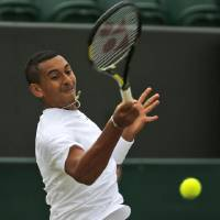 Photo - Nick Kyrgios of Australia plays a return to Richard Gasquet of France during their match at the All England Lawn Tennis Championships in Wimbledon, London, Thursday, June 26, 2014. (AP Photo/Pavel Golovkin)