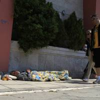 Photo - Pedestrians walk by a homeless man in Thessaloniki, Greece, Sunday, April 21. 2013. Under an international bailout deal that saved it from bankruptcy in 2010, Greece agreed to slash bloated budget deficits, repeatedly cutting pensions and salaries while hiking taxes. (AP Photo/Nikolas Giakoumidis)