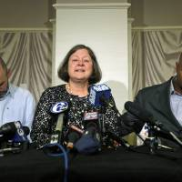 Photo - FILE - In this April 9, 2013, file photo, former NFL player Dorsey Levens, right, extends a hand as Mary Ann Easterling, the widow of former NFL player Ray Easterling, reacts as former NFL player Kevin Turner, left, looks on during a news conference in Philadelphia, after a hearing to determine whether the NFL faces years of litigation over concussion-related brain injuries. Judge Anita Brody has announced on Thursday, Aug. 29, 2013, that the NFL and more than 4,500 former players want to settle concussion-related lawsuits for $765 million. (AP Photo/Matt Rourke, File)