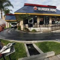 Photo - In this Thursday, April 25, 2013, photo, a pedestrian walks past a Burger King restaurant near downtown Los Angeles. Burger King reports their quarterly earnings on Friday, April 26, 2013. (AP Photo/Nick Ut)