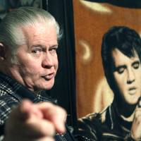 Photo - FILE - In this Dec. 9, 2009 file photo, Paul MacLeod stands before a poster of Elvis Presley in the antebellum home and a private Elvis Presley museum he calls