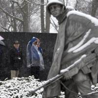 Photo - Visitors view the Korean War Memorial during a snow storm in Washington, Tuesday, March 25, 2014. The calendar may say it's spring, but the mid-Atlantic region is seeing snow again. The National Weather Service has issued a winter weather advisories for much of the region Tuesday. The advisories warn that periods of snow could make travel difficult, with slippery roads and reduced visibility. (AP Photo/ Evan Vucci)