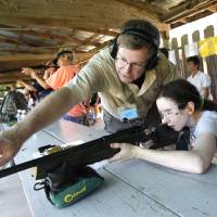 Photo - Michelle Hellstern receives rifle instruction from Dr. Stephen Veronneau during the annual Women's Only Fun Shoot at the Oklahoma City Gun Club north of Arcadia, OK, Saturday, September 7, 2013,  Photo by Paul Hellstern, The Oklahoman