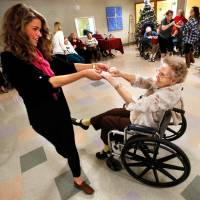 Photo - Kappa Alpha Theta sorority member Kirby Olson invites Grace Living Center resident Christine Ernest to dance at a party organized by members of the University of Oklahoma sorority.