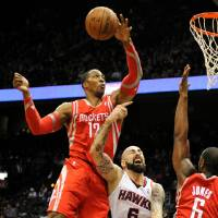 Photo - Houston Rockets' Dwight Howard (12) fouls Atlanta Hawks forward Paul Millsap (4) on the block with Terrence Jones (6) in the first half of an NBA basketball game on Friday, Jan. 10, 2014, in Atlanta. (AP Photo/David Tulis)