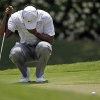 Photo -   Tiger Woods bows his head while waiting his turn on the ninth green during the third round of the Players Championship golf tournament at TPC Sawgrass, Saturday, May 12, 2012, in Ponte Vedra Beach, Fla. (AP Photo/David Goldman)