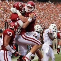 Photo -   Oklahoma quarterback Blake Bell (10) celebrates his touchdown with teammate Brannon Green (82) as Trey Millard (33) looks on and Texas linebacker Demarco Cobbs (7) walks off during the first half of an NCAA college football game at the Cotton Bowl Saturday, Oct. 13, 2012, in Dallas. (AP Photo/Michael Mulvey)