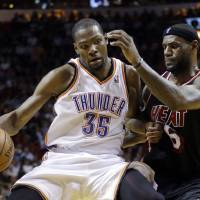 Photo - Miami Heat small forward LeBron James (6) puts pressure on Oklahoma City Thunder small forward Kevin Durant (35) during the fourth period of an NBA basketball game in Miami, Wednesday, Jan. 29, 2014. The Thunder won 112-95. (AP PhotoAlan Diaz)