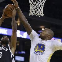 Photo - Brooklyn Nets' Alan Anderson (6) shoots against Golden State Warriors' Marreese Speights during the first half of an NBA basketball game Saturday, Feb. 22, 2014, in Oakland, Calif. (AP Photo/Ben Margot)