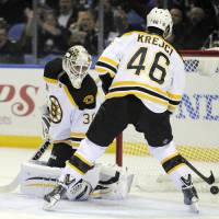 Photo - Boston Bruins goaltender Chad Johnson (30) looks back into the net after a goal by Buffalo Sabres' Zemgus Girgensons as Bruins center David Krejci (46) arrives too late during the first period of an NHL hockey game in Buffalo, N.Y., Wednesday, Feb. 26, 2014. (AP Photo/Gary Wiepert)