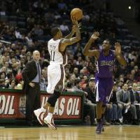 Photo - Milwaukee Bucks' Monta Ellis (11) hits a half-court shot at the end of the first quarter as Sacramento Kings' Tyreke Evans(13) defends during a NBA basketball game on Wednesday, Dec. 12, 2012, in Milwaukee. Bucks head coach Scott Skiles, left, watches the play. (AP Photo/Jeffrey Phelps)