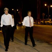 Photo - Escorted by security, U.S. Secretary of State John Kerry, left, walks with Frank Lowenstein, senior advisor to the secretary on Middle East issues, through the streets of Jerusalem just after 4 a.m. on Sunday, June 30, 2013 after finishing a meeting with Israeli Prime Minister Netanyahu that took over six hours. After the marathon meeting, Kerry decided to get some air by walking to a park near the hotel where he is staying and the meeting was held. Kerry is shuttling between Palestinian and Israeli leaders in hopes of restarting peace talks. (AP Photo/Jacquelyn Martin, Pool)