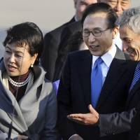 Photo -   FILE - In this Oct. 14, 2011 file photo, Chicago Mayor Rahm Emanuel, right, greets South Korean President Lee Myung-bak and his wife Kim Yoon-Ok on their arrival at O'Hare International Airport for a visit to Chicago. Emanuel and the city will be in the international spotlight when it hosts the NATO summit May 20-21, 2012. Myung-bak is among the 50 heads of state expected to attend. (AP Photo/Paul Beaty, File)